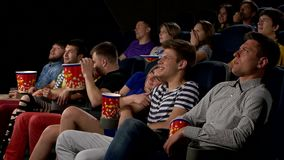 Young people watch movies in cinema: horror stock video footage