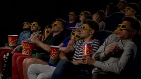 Young people watch movies in cinema: horror in 3D stock footage