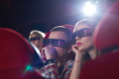 Young people watching 3D film at the movie theatre stock images