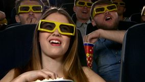 Young people watching 3d movie at movie theater stock video footage