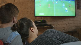 Young people watching football on TV and drinking beer. The girl put her head on her boyfriend`s shoulder. Young couple relaxing and have a good time. The stock footage