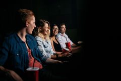 Young people watching movie in cinema. Group of friends sitting in multiplex movie theater and watching movie. Happy young people watching movie in cinema Royalty Free Stock Image
