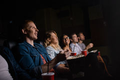 Young people watching movie in cinema. Group of friends sitting in multiplex movie theater with popcorn and drinks. Young people watching movie in cinema Royalty Free Stock Photos