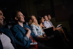 Young people watching movie in cinema. Group of friends sitting in multiplex movie theater with popcorn and drinks. Young people watching movie in cinema hall Stock Image