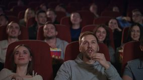 Young people watching movie in cinema theater. Cinema people emotion stock footage