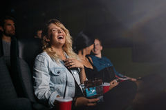 Young people watching movie and laughing. Group of friends sitting in multiplex movie theater and watching comedy movie. Young people watching movie in cinema Royalty Free Stock Images