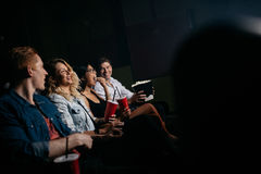 Young people watching movie in multiplex theater. Group of friends sitting in multiplex movie theater with popcorn and drinks. Young people watching movie in Stock Image