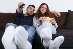 Young people watching television on the sofa Royalty Free Stock Photography