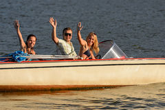 Young people waving from motorboat Royalty Free Stock Photography