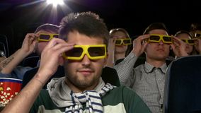 Young people wear 3D glasses to watch a movie at. Company young mans and womans watching movie at cinema: comedy, all laughing, eating popcorn. people wear 3D stock video footage