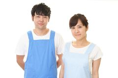 Smiling man with woman. Young people wearing apron isolated on white background stock images