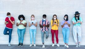 Free Young People Wearing Face Safety Masks Using Smart Mobile Phones While Keeping Social Distance During Coronavirus Time - Stock Photography - 188277332