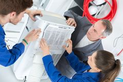Young people woking on air conditioning unit Royalty Free Stock Photos
