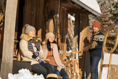 Young people by wooden winter cottage sunny royalty free stock photo