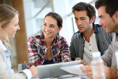 Young people working on tablet in meeting Royalty Free Stock Image