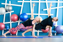 Young people in yoga class in Extended Side Angle Pose. Yoga group concept. Nice couple doing yoga in a studio. Young people in yoga class in Extended Side Angle stock photos