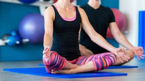 Young people in yoga class in lotus position. Yoga group concept. Nice couple doing yoga in a studio. Young people in yoga class in lotus position. Yoga group stock photography