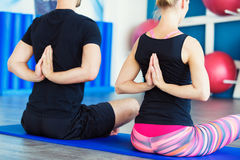 Young people in yoga class in Reverse Prayer Pose. Yoga group concept. Nice couple doing yoga in a studio. Young people in yoga class in Reverse Prayer Pose Royalty Free Stock Photography