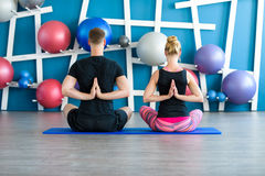 Young people in yoga class in Reverse Prayer Pose. Yoga group concept. Nice couple doing yoga in a studio. Young people in yoga class in Reverse Prayer Pose Royalty Free Stock Photos
