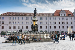 Young peple sitting at the town square of Augsburg. Stock Photos