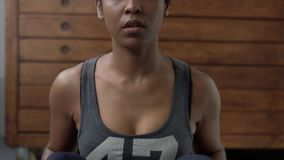 Young perfect fitting mixed race woman during her abs routine in sunny loft. Front view closeup stock video footage