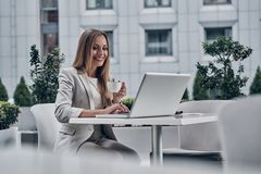 Young perfectionist. Beautiful young woman using laptop and drinking coffee while sitting in the modern restaurant stock photography