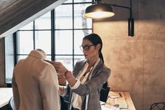 Young perfectionist. Serious young woman in eyewear adjusting a. Collar of the jacket on mannequin while standing in her workshop Royalty Free Stock Images
