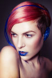 Young person with blue eye shadows, blue ears and pink hair with blue strand on it looking at camera and hands near face Royalty Free Stock Photo