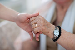 When young person is helping the old ones. Young person is holding a hand of an old person Royalty Free Stock Photography