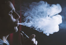 Young person holding electronic cigarette or e cig and vaping cl. Cloud of vaping electronic cigarette device or e cig by a young man royalty free stock photo