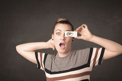 Young person holding paper with angry eye drawing. Concept Royalty Free Stock Image