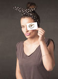 Young person holding paper with angry eye drawing. Concept Stock Photo