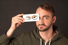 Young person holding paper with angry eye drawing. Concept Royalty Free Stock Images