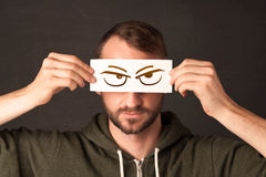 Young person holding paper with angry eye drawing Stock Photos