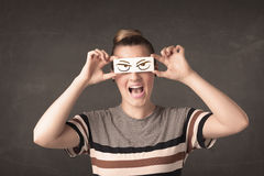Young person holding paper with angry eye drawing Royalty Free Stock Photo