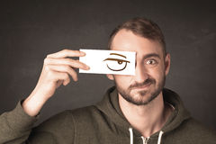 Young person holding paper with angry eye drawing. Concept Stock Image