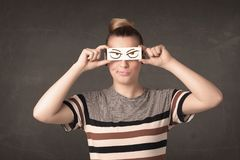 Young person holding paper with angry eye drawing royalty free stock image