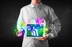 Young person holding tablet with graph and chart symbols Royalty Free Stock Image