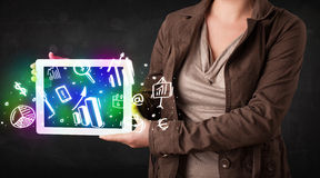 Young person holding tablet with graph and chart symbols Royalty Free Stock Photography