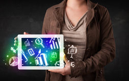 Young person holding tablet with graph and chart symbols Royalty Free Stock Photos
