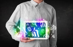 Young person holding tablet with graph and chart symbols Stock Photo