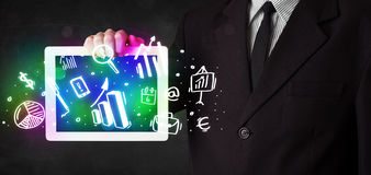 Young person holding tablet with graph and chart symbols Stock Photos