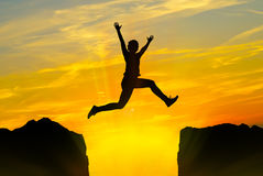 Young person jumping over the mountains Stock Image