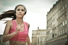 Young person listening misic. Person (young beautiful woman) listening music running (jogging) in city street Stock Photography