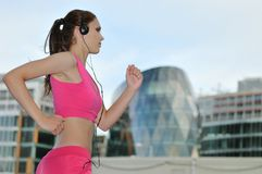 Young person listening msic running on street. Person (young beautiful woman) listening music running (jogging) in city street Royalty Free Stock Images
