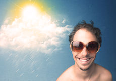 Young person looking with sunglasses at clouds and sun. Concept on blue background Stock Image