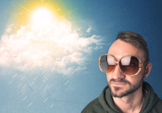 Young person looking with sunglasses at clouds and sun Royalty Free Stock Images