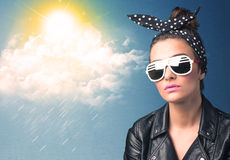 Young person looking with sunglasses at clouds and sun. Concept on blue background Stock Photo