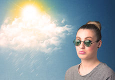 Young person looking with sunglasses at clouds and sun Stock Images