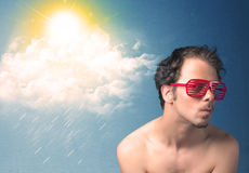 Young person looking with sunglasses at clouds and sun Stock Photo
